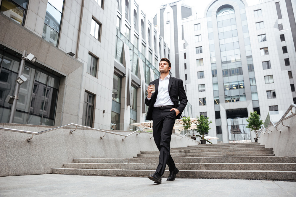 Confident young businessman walking and drinking coffee near business center