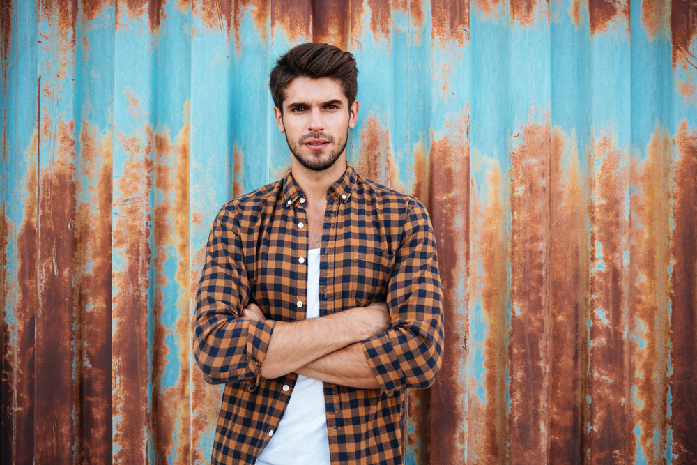 Confident young man in checkered shirt standing with arms crossed over blue metal background with rust