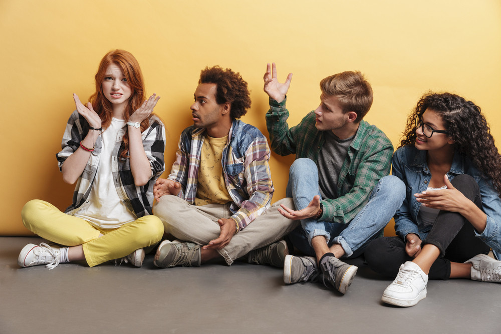 Confused redhead girl with her shocked amazed friends sitting over yellow background