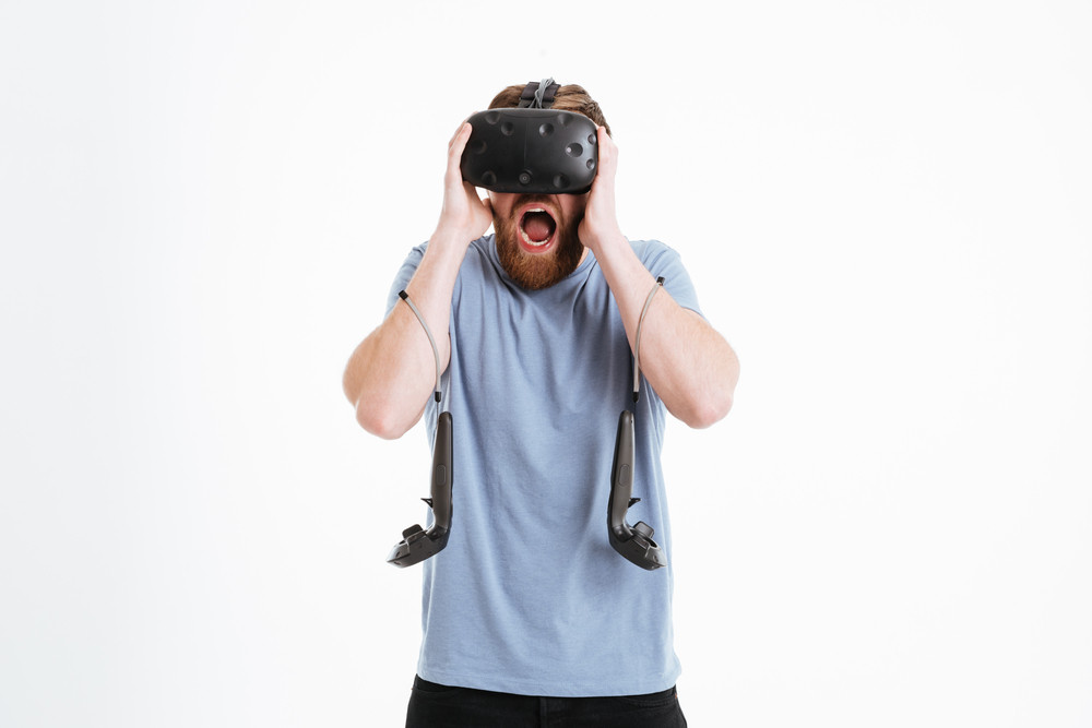Confused screaming bearded young man wearing virtual reality device standing over white background