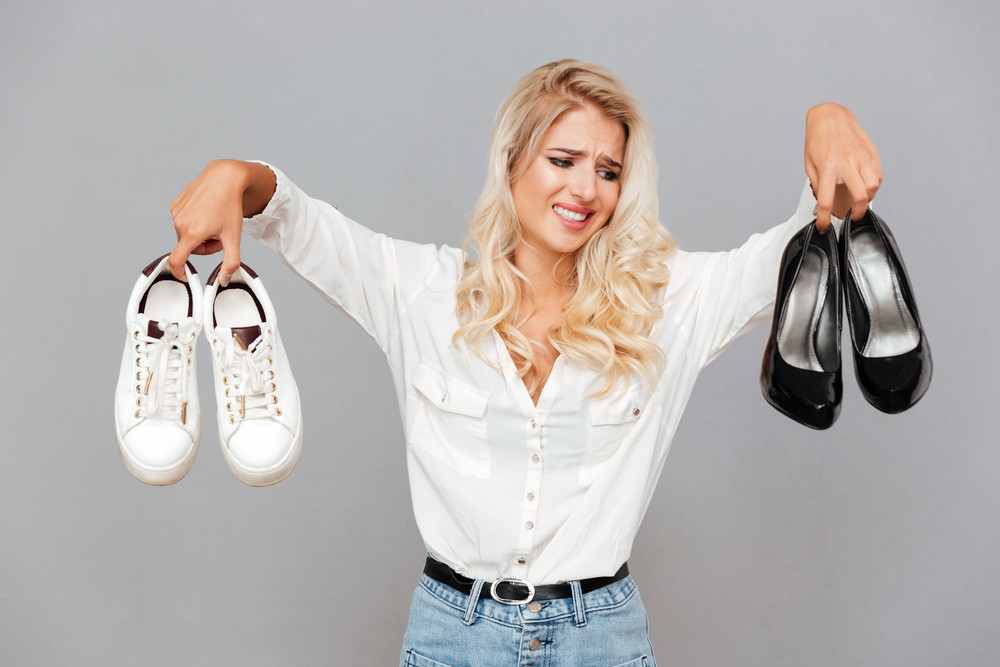 Confused young girl choosing shoes over gray background