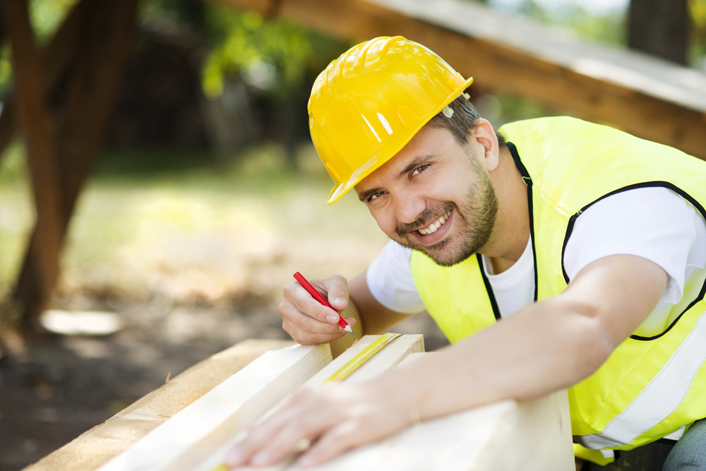 Construction worker is working with wooden beam