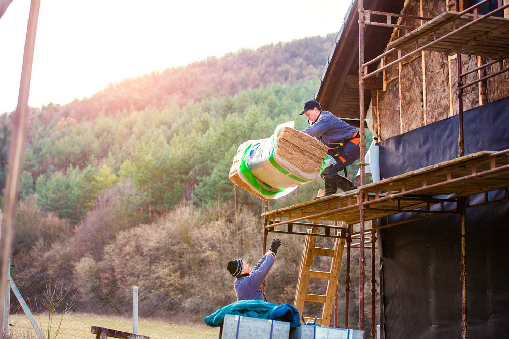 Construction worker standing on scaffold thermally insulating house facade with glass wool. Other worker passing him another bale up on platform.