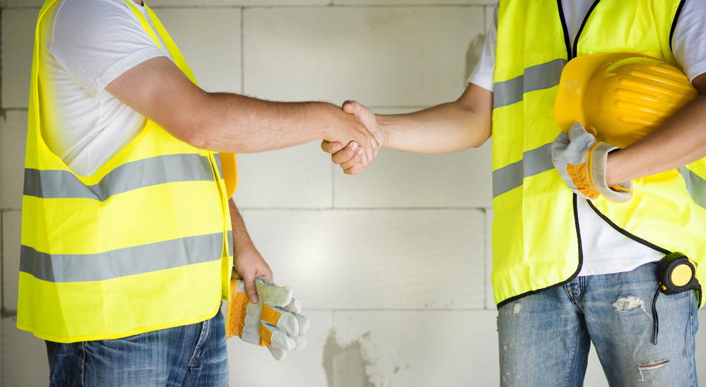Construction workers collaborating on new house building