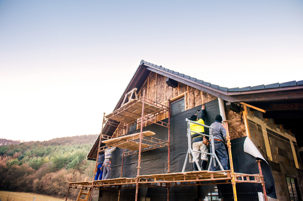Construction workers standing on scaffold thermally insulating house facade with glass wool and black foil.