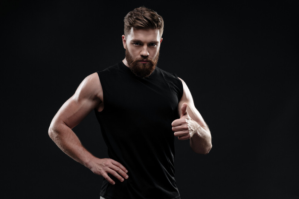 Cool athletic man in studio. shows finger up. isolated dark background