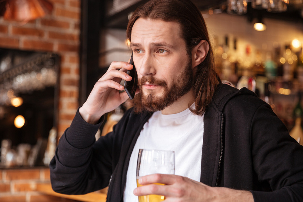 Cool bearded man talking on phone near the bar with cup of beer