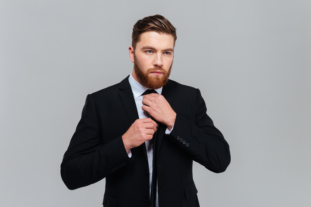 Cool business man in black suit tying a tie in studio. Isolated gray background