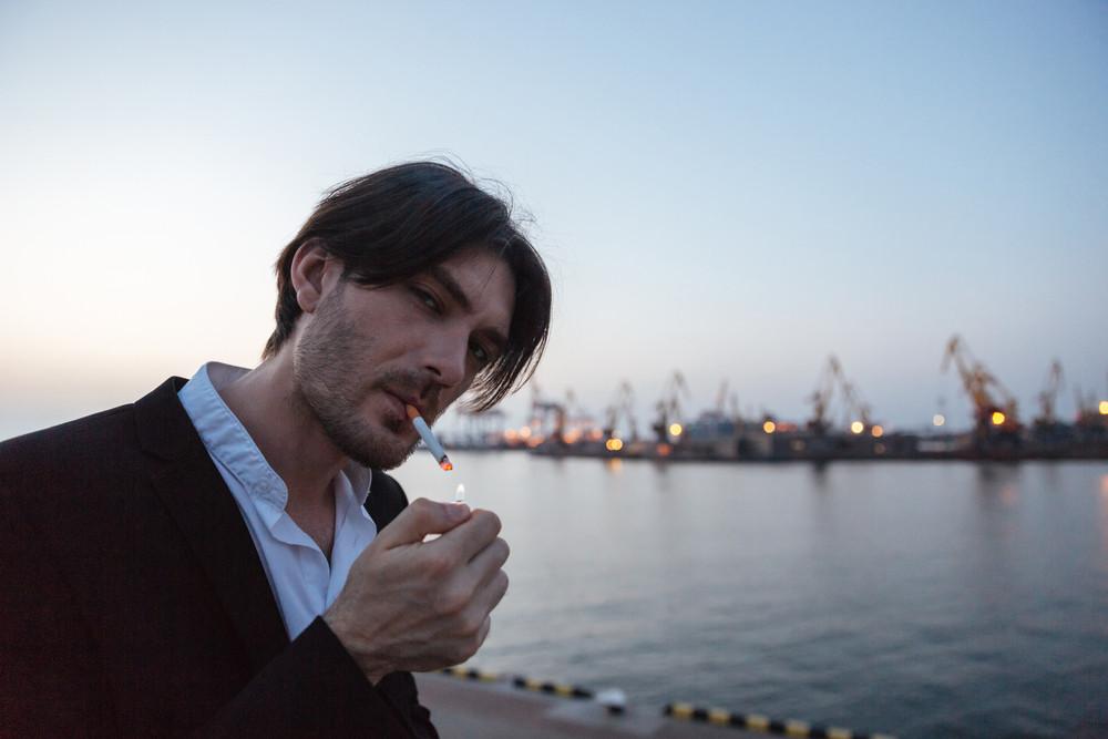 Cool man in port. smoking cigarette. Odessa port