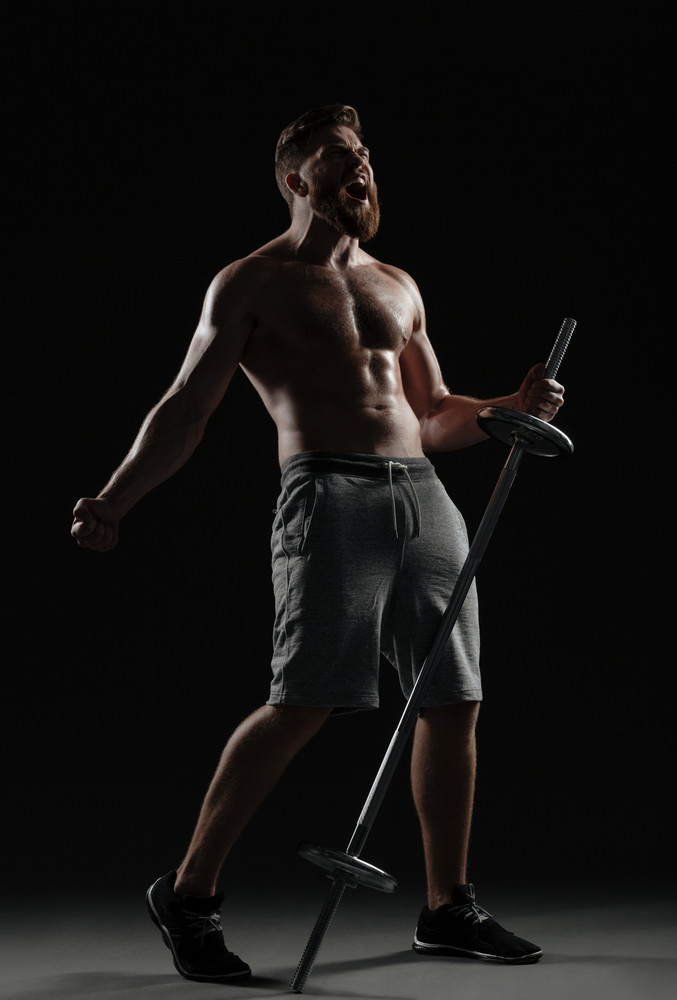 Cool muscular man with barbell. full length portrait. isolated dark background