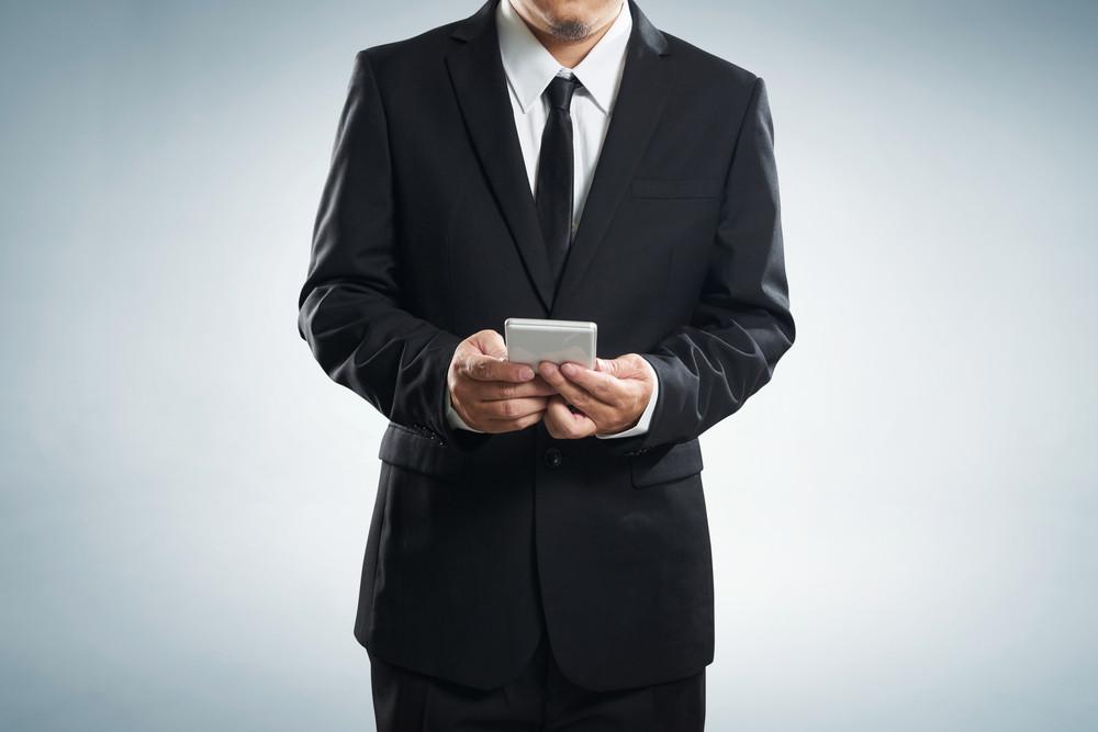 Corporate male executive messaging via phone