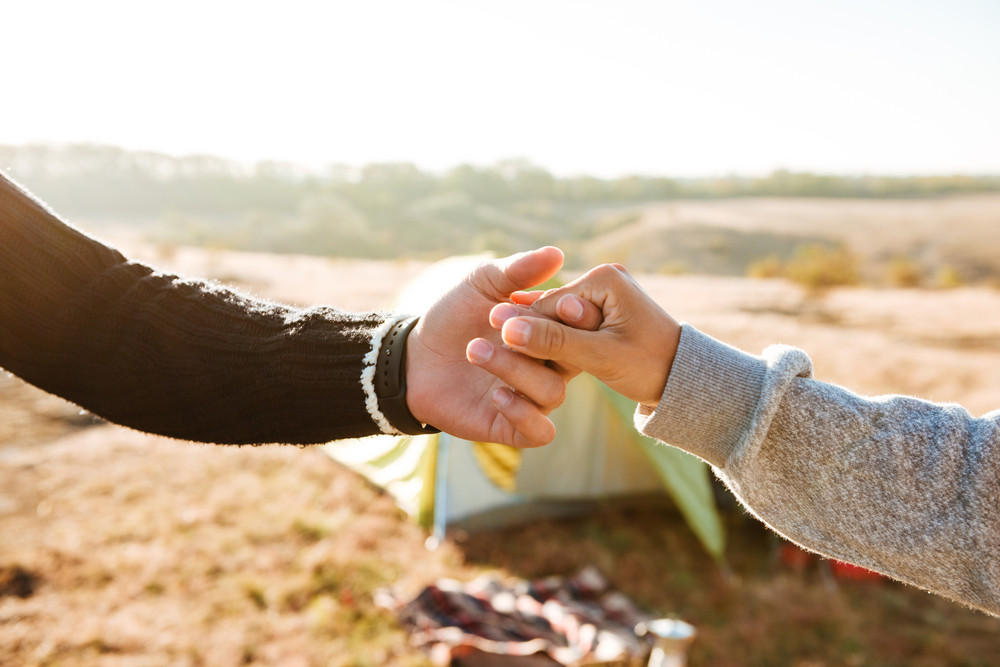 Couple holding hands near the tent. cropped image  sc 1 st  Storyblocks & Couple holding hands near the tent. cropped image Royalty-Free ...