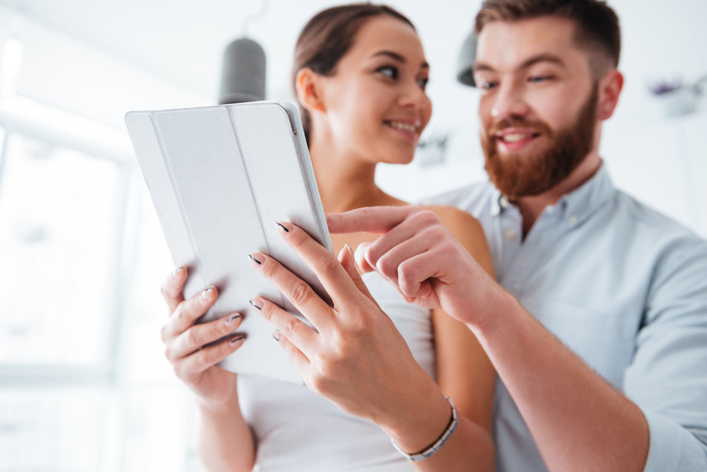 Couple in kitchen with tablet. man hugs girl from behind