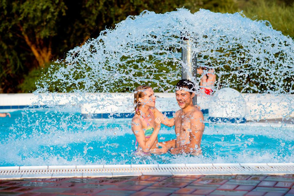 Couple in swimmning pool having fun under splashing fountain. Summer heat and water.