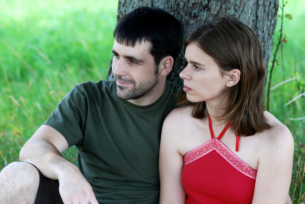 Couple is resting under tree.