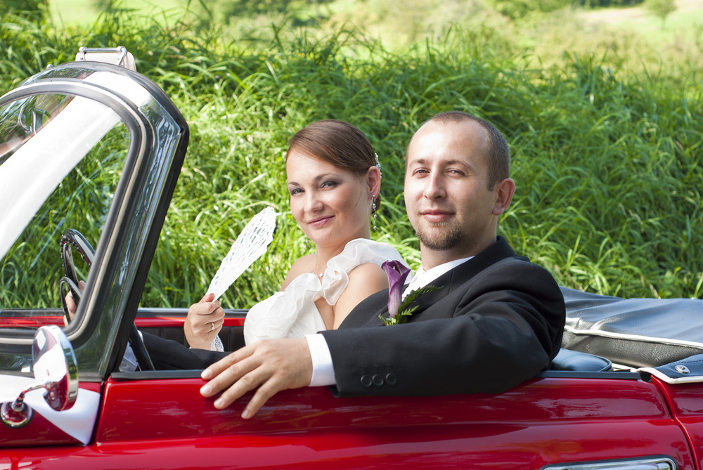 Couple is riding red retro car.