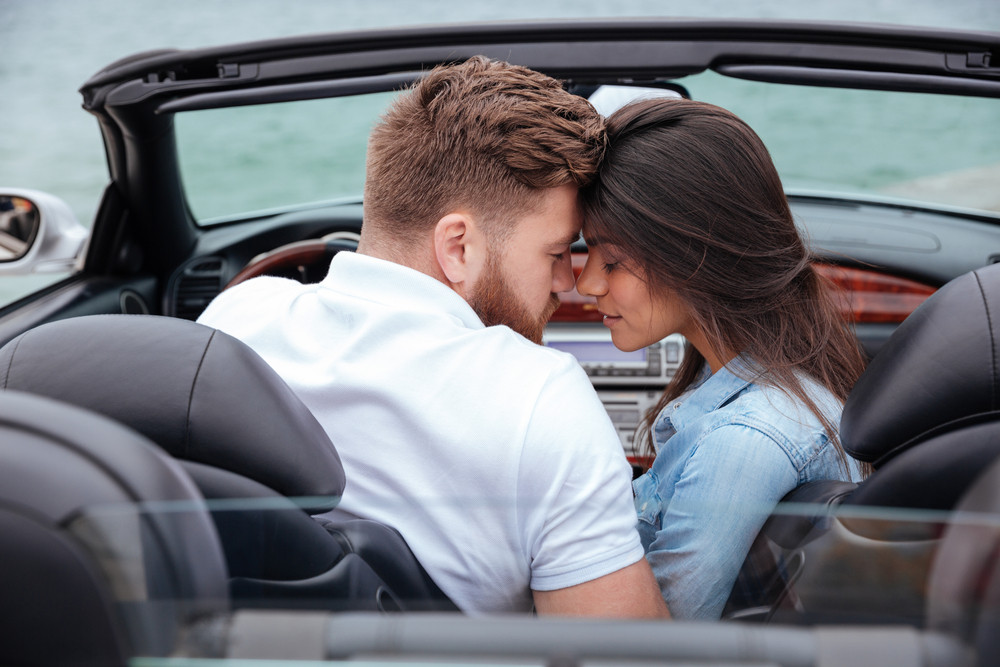 Couple lkissing in white cabriolet outdoors
