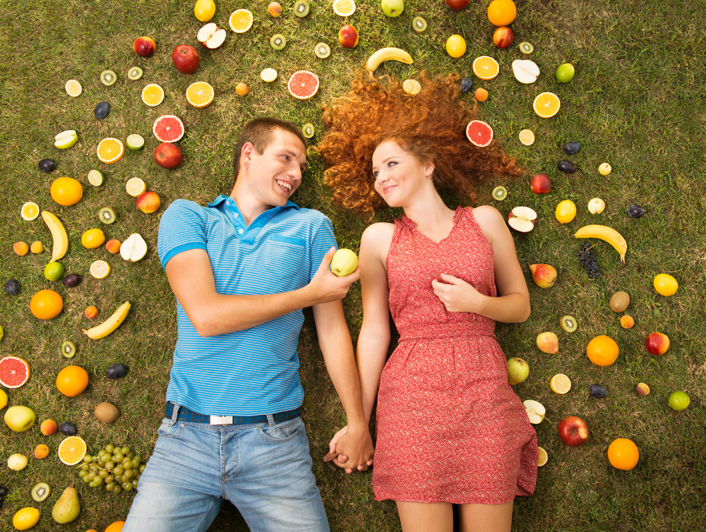 Couple with fruit is lying on the grass