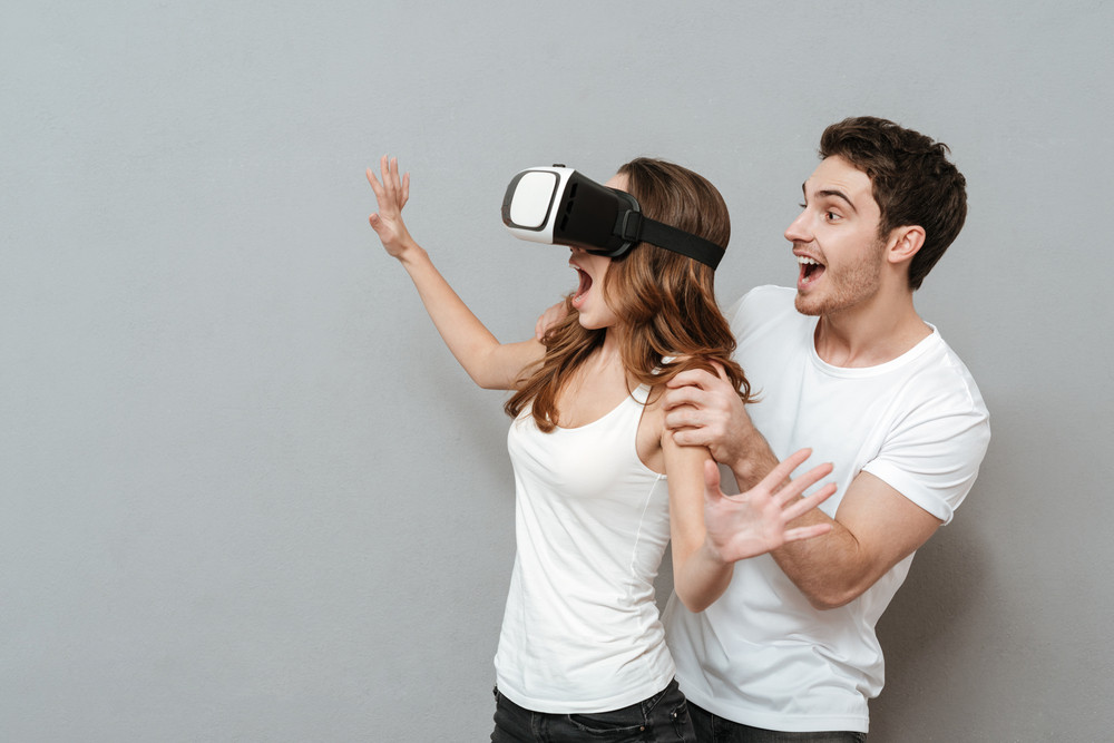 Couple with virtual reality device in studio. Woman using device and man standing from the her back. Isolated gray background