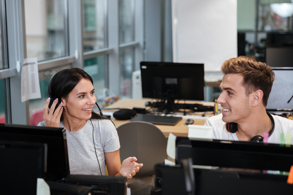 Coworkers in white t-shirts sit by the table in headphones and look eyes to eyes. Call center