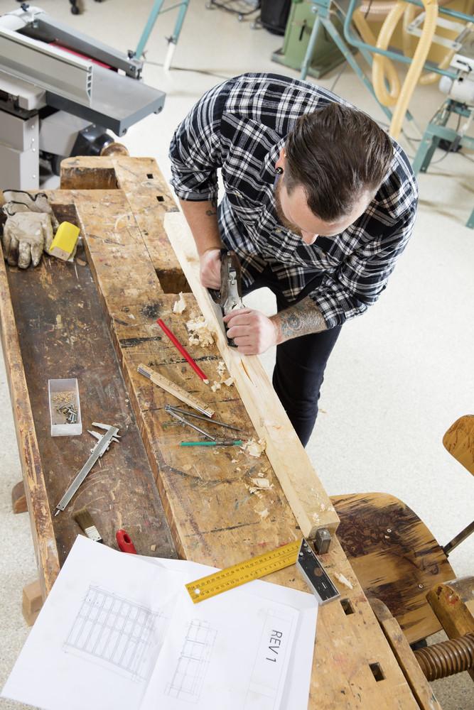 Craftsman work with plane on wood plank in workshop