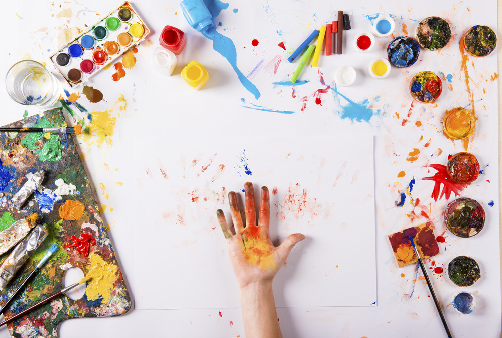 Creative art concept with colorful paints over white paper