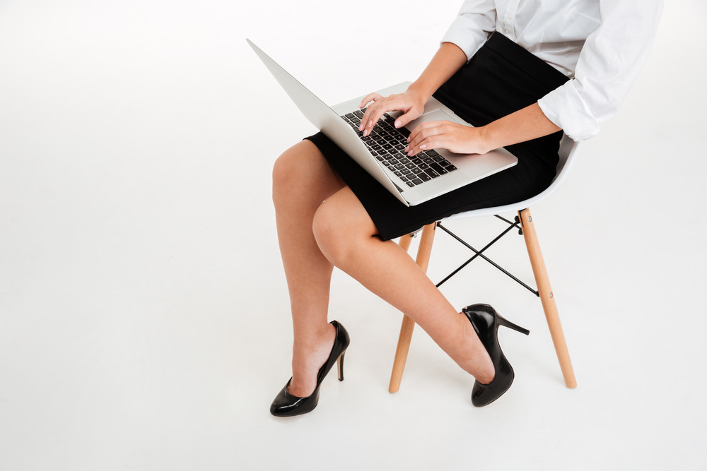 Cropped image of a businesswoman using laptop on the office chair isolated on a white background
