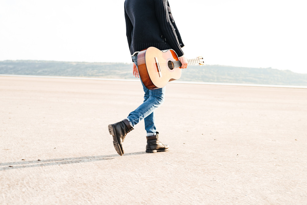 Cropped image of a casual man holding guitar and walking across seashore