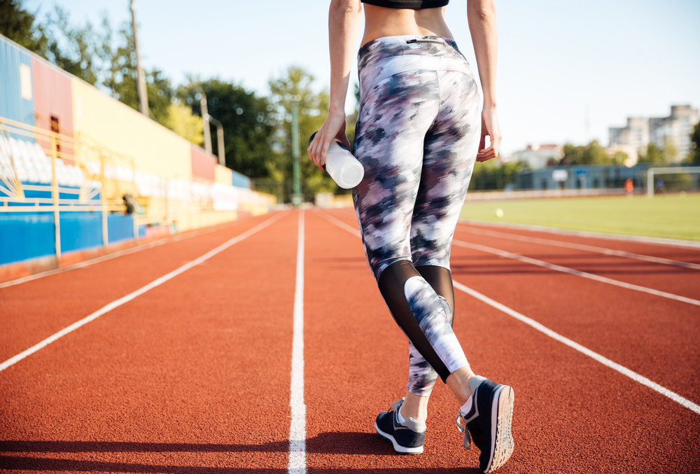 Cropped image of a fitness woman holding water bottle at the stadium