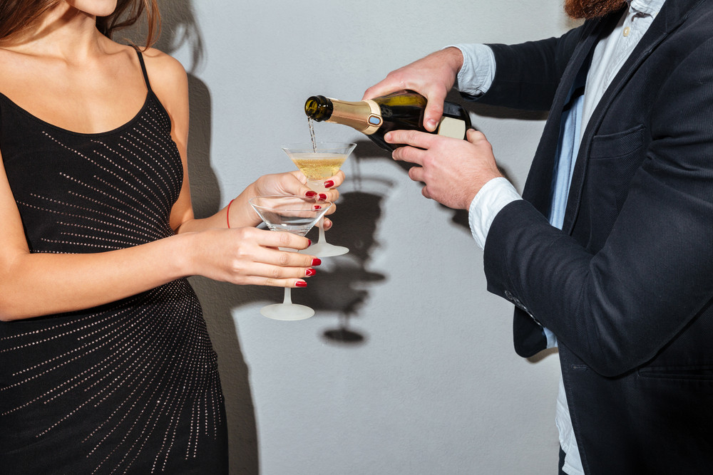 Cropped image of a male pouring champagne into glasses holding by a female over gray background