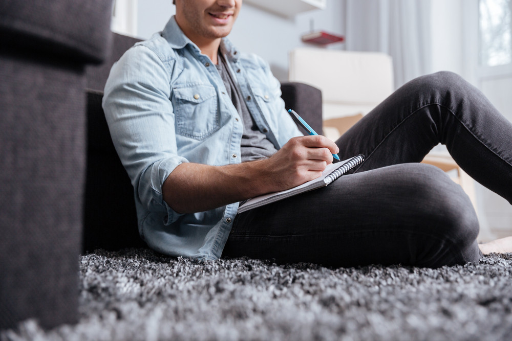 Cropped image of a man in casual wear writting in copybook while sitting on the carpet at home