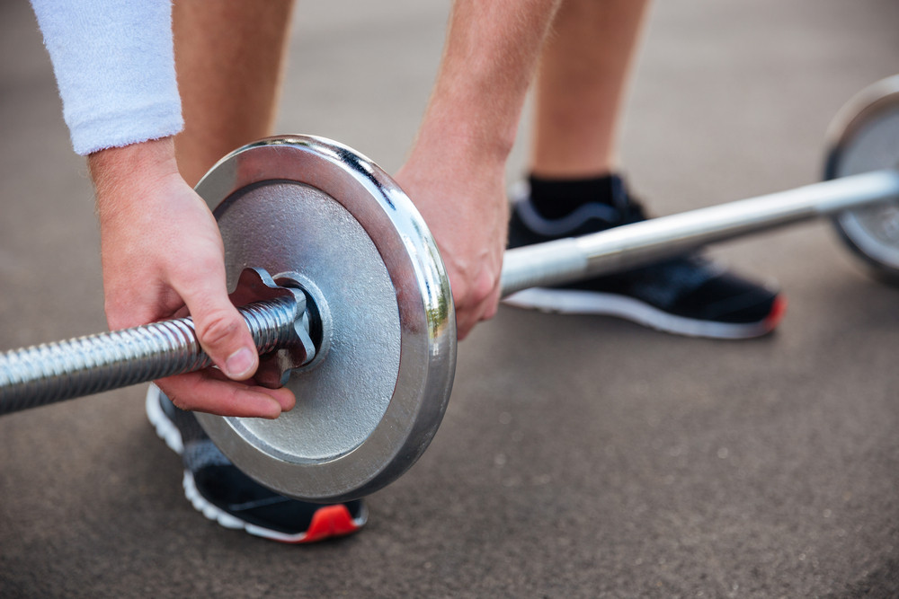 Cropped image of a muscular fitness man going to lift heavy barbell outdoors