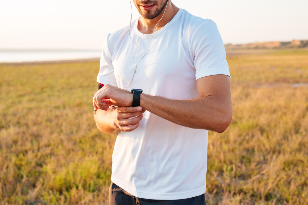 Cropped image of a sports man looking at his smartwatch with earphones