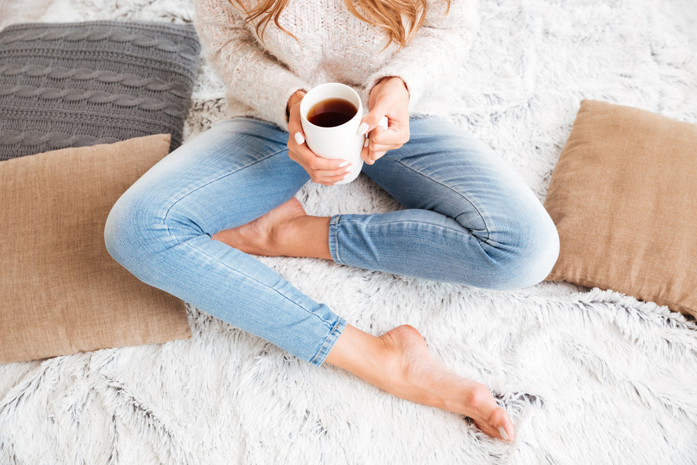 Cropped image of a woman in sweater and jeans holding tea cup while sitting with legs crossed indoors