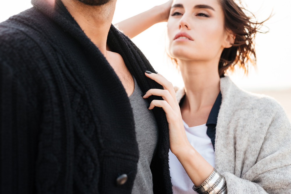 Cropped image of a young casual couple over white background