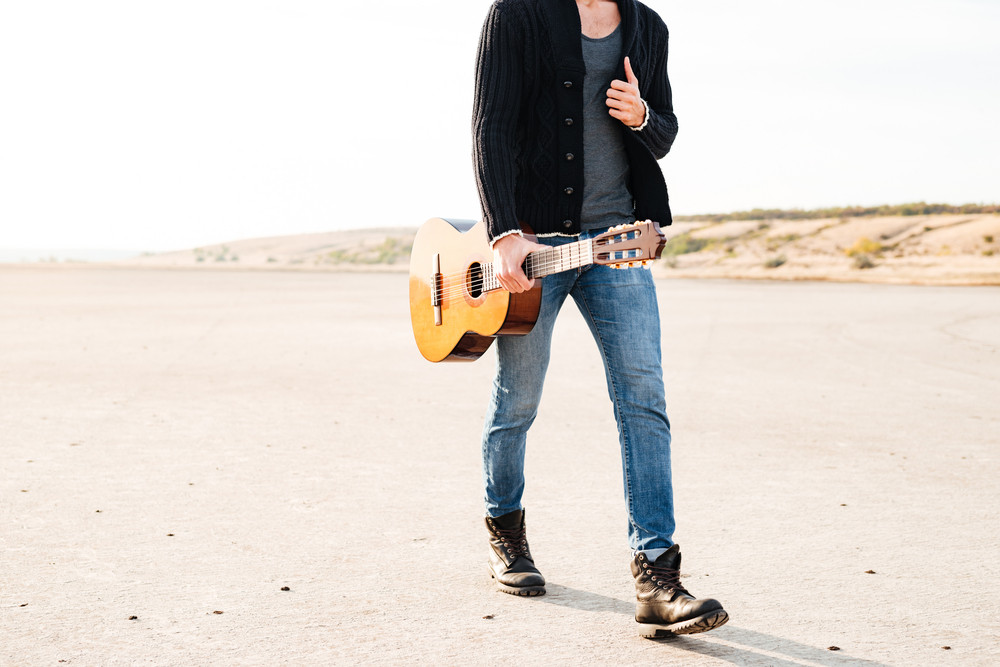 Cropped image of a young casual man walking with guitar at the seaside