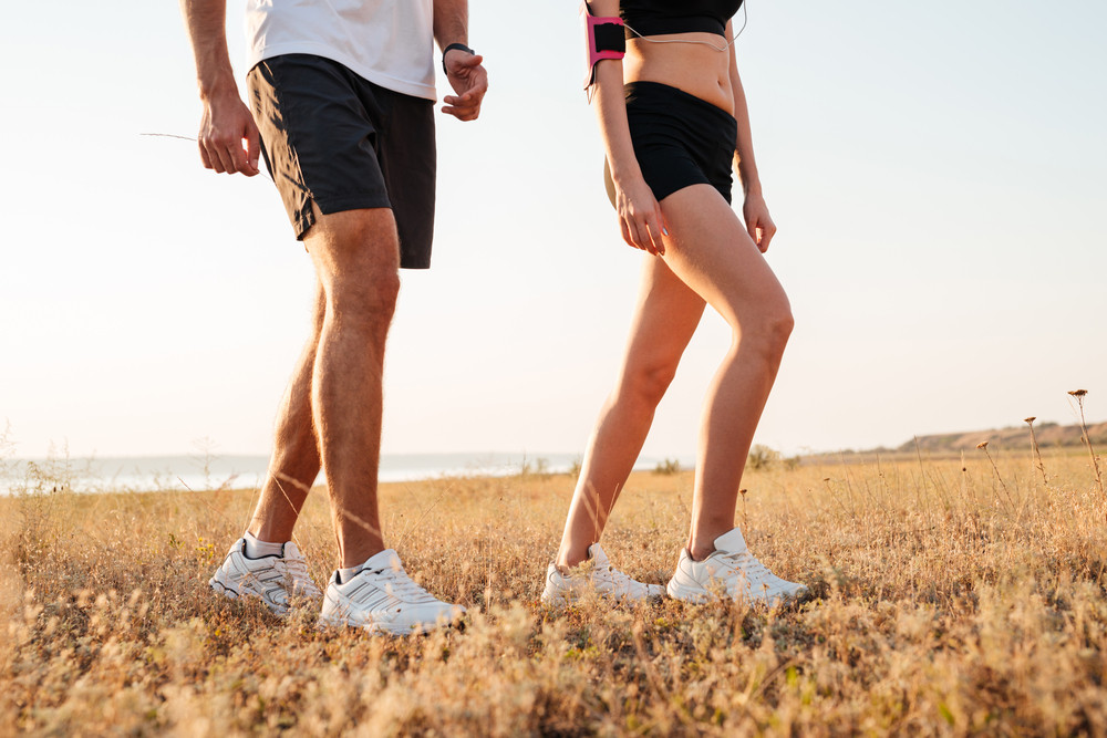 Cropped image of a young fit fitness couple walking on hill