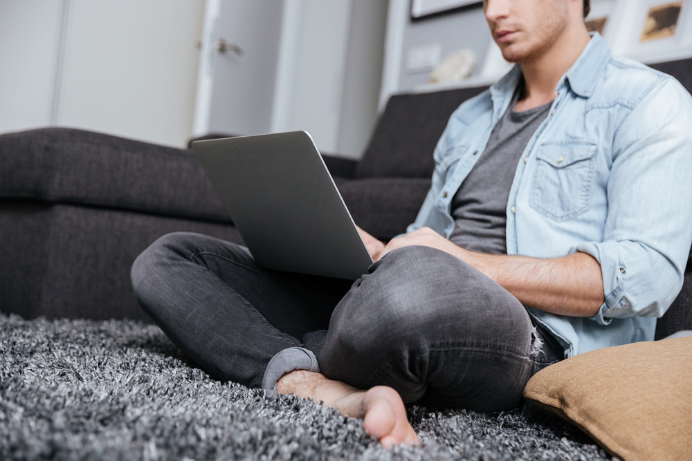 Cropped image of a young pensive man working with laptop computer while sitting on carpet at home