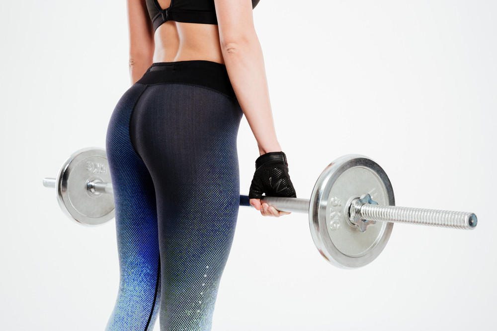 Cropped image of a young sexy woman exercising with barbell isolated on a white background