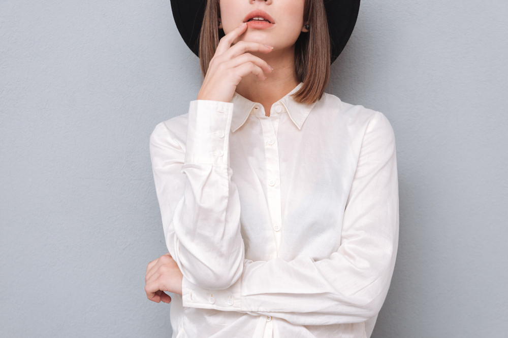 Cropped image of a young stylish woman in hat and shirt posing isolated on a gray background