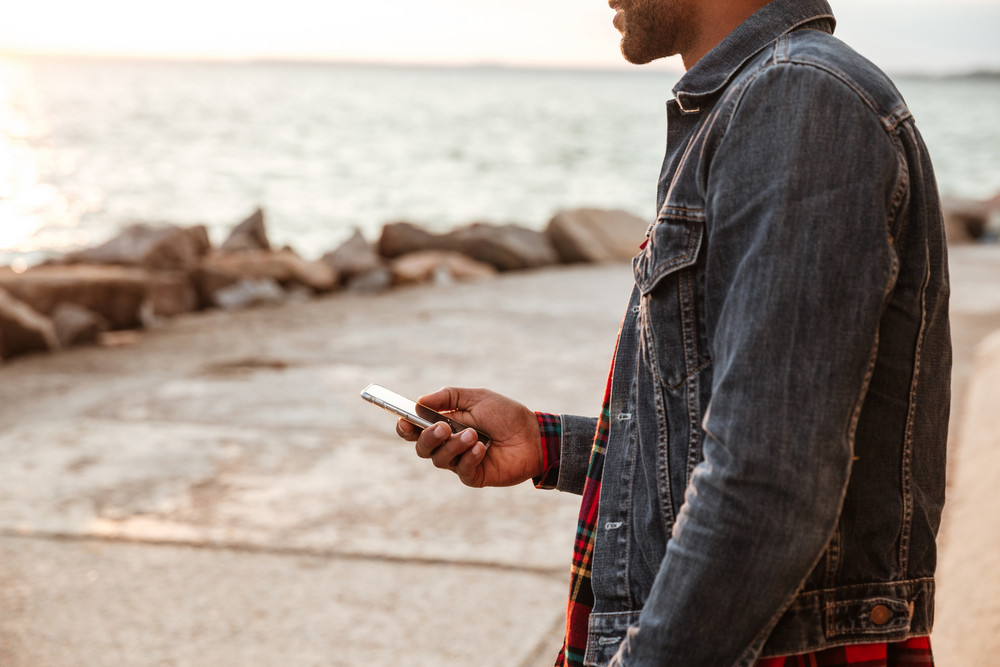 Cropped image of african man walking on beach and chatting by phone.