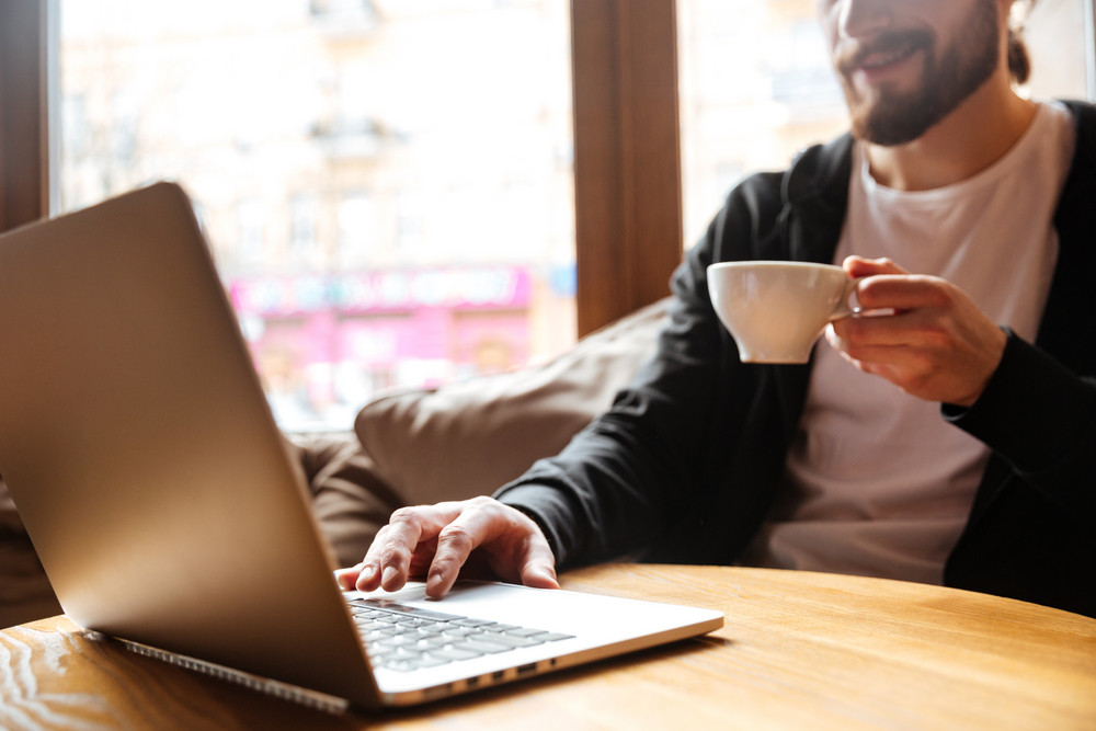 Cropped image of Bearded man sitting by the table with coffee and using laptop in cafe with window on background