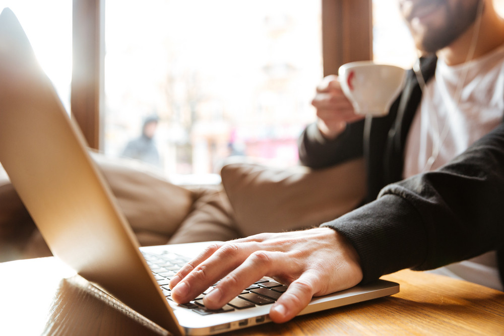 Cropped image of Bearded man sitting by the table with laptop computer and coffee in hand in cafe near the window