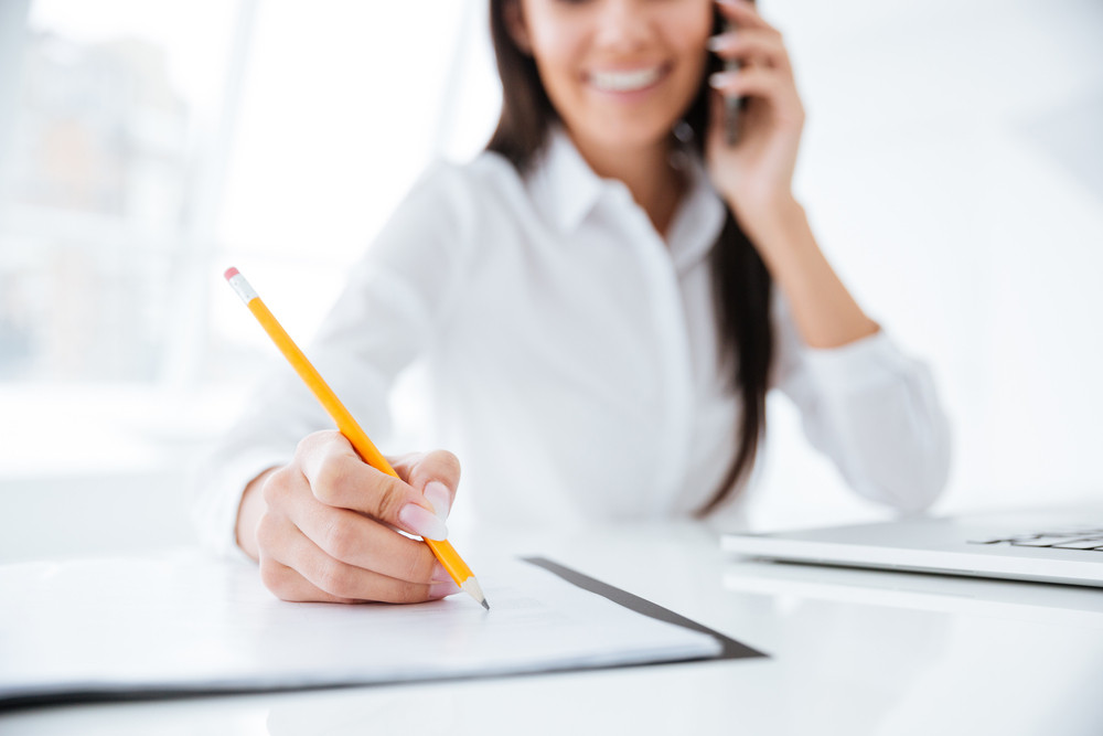 Cropped image of Business woman talking at phone and writing something in documents by the table in office. Focus on documents