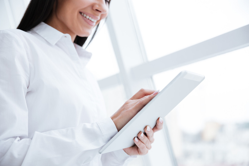 Cropped image of Business woman using tablet computer and standing near the window in office