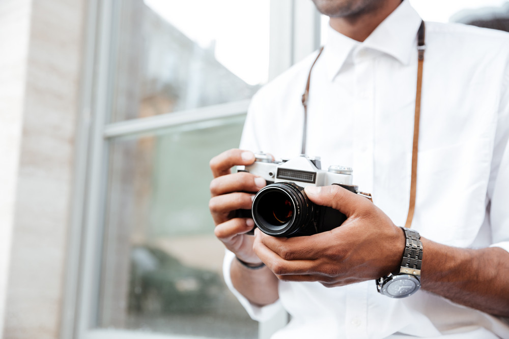 Cropped Image of fashion black man on the street. with camera
