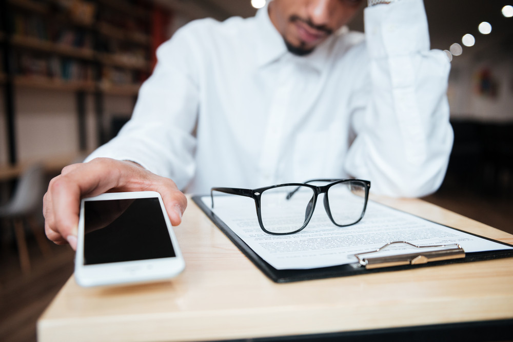 携帯電話を保持しているテーブルに座ってハンサムなアフリカのビジネスマンのクロップド画像。コワーキング。