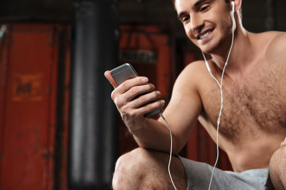 Cropped image of happy man sitting in a gym while listen to music by phone. Focus on hands.