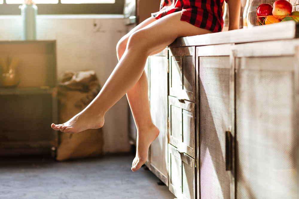 Cropped image of Legs of woman in kitchen. Girl sitting on table. Side view
