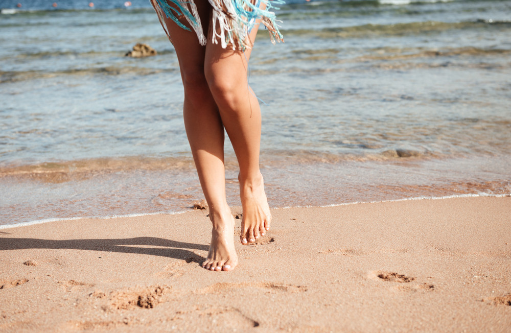 Cropped image of legs of woman which walking on the beach